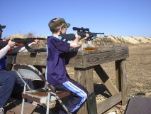Spy-Man firing a .22 rifle